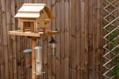 Tabella d'alimentazione dell'uccello contro una rete fissa di legno Fotografia Stock