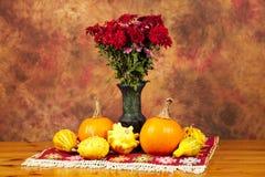 Tabella decorata con la coperta, i fiori di autunno, le zucche e le zucche rossi Immagini Stock