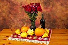 Tabella decorata con la coperta rossa, i fiori di autunno, la bottiglia di vino, le zucche e le zucche Immagini Stock