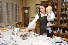 Tabella della regolazione della donna con il suo bambino Immagini Stock Libere da Diritti