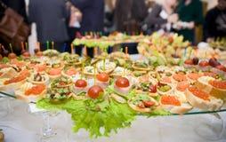 Tabella di banchetto piena, mangiante la gente nella priorità bassa immagine stock