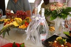 Tabella di cerimonia nuziale Due hanno decorato le bottiglie di champagne, dei frutti e del mazzo del ` s della sposa Fotografie Stock Libere da Diritti