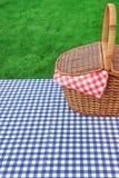 Tabella di picnic rustica all'aperto con il paniere e la tovaglia blu immagine stock
