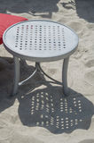 Tabella di plastica in sabbia accanto all'ombra della colata della chaise-lounge della spiaggia Immagine Stock