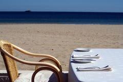 Tabella di pranzo vuota sulla spiaggia Immagine Stock