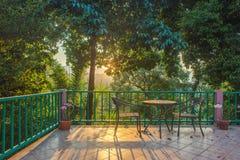 Tabella e sedia sulla piattaforma di legno nel giardino con il tramonto Fotografia Stock