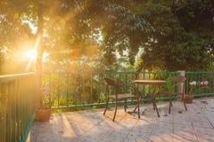Tabella e sedia sulla piattaforma di legno nel giardino con il tramonto Immagine Stock Libera da Diritti