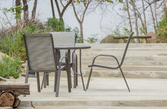 Tabella e sedie che stanno sul pavimento del cemento nel giardino Immagine Stock