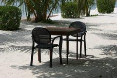 Tabella e sedie vuote sulla spiaggia Fotografia Stock