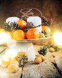 Tabella festiva con i mandarini, pigne, noci, candele su fondo di legno Luce di Natale immagine stock libera da diritti