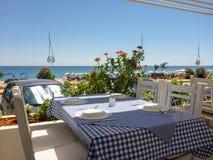 Tabella nella locanda vicino alla bella spiaggia di Skala dell'isola di Kefalonia, mare ionico, Grecia fotografia stock