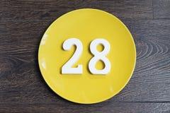 Tabelle achtundzwanzig auf der gelben Platte Stockbild