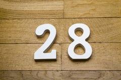 Tabelle achtundzwanzig auf einem hölzernen, Parkettboden Lizenzfreies Stockbild