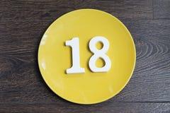Tabelle achtzehn auf der gelben Platte Stockfotos