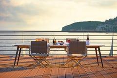 Tabelle auf der Terrasse bei Sonnenuntergang Lizenzfreies Stockfoto
