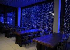 Tabelle in caffè Le luci nelle finestre Tempo di sera immagine stock