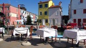 Tabelle dei turisti aspettanti di un ristorante della via La passeggiata sull'isola di Burano, Venezia video d archivio