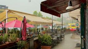 Tabelle del caffè accogliente della via che diventa bagnato in pioggia di versamento, clima di Georgia stock footage