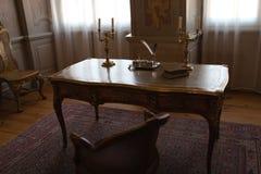 Tabelle des königlichen Palastes in einem Kabinettraum mit Stühlen und Feder lizenzfreies stockfoto