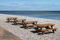 Tabelle di picnic sulla spiaggia immagini stock