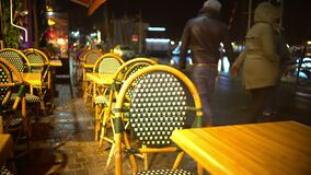 Tabelle e sedie del ristorante vuoto della via, la gente che cammina vicino, notte piovosa video d archivio