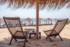 Tabelle e sedie installate nella spiaggia Posta di legno con l'ombrello tropicale che sta sopra Brezza dell'oceano che ondeggia l fotografie stock libere da diritti