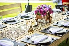 Tabelle eingestellt mit Blumenmittelstück Lizenzfreie Stockfotos