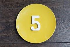Tabelle fünf auf der gelben Platte Lizenzfreie Stockfotos