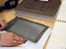 Tabelle für Blindenschrift-Handschrift Lese- und Schreibenshilfen für die Vorhänge auf Buch-Welt Prag 2019 lizenzfreie stockfotos