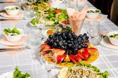 Tabelle gezeichnet mit Vielzahl von Tellern, von denen das Mittelstück Teller mit geschnittener Frucht ist stockfotografie