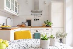 Tabelle im stilvollen weißen Kücheninnenraum, wirkliches Foto stockfotos