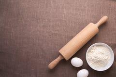 Tabelle mit Backenbestandteilen Mehl, Eier, Weizen und Nudelholz auf Tischdecke Lizenzfreie Stockfotografie