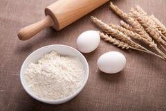 Tabelle mit Backenbestandteilen Mehl, Eier, Weizen und Nudelholz auf Tischdecke Stockfotos