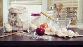 Tabelle mit Backenbestandteilen Vorbereiten von Lebensmittelinhaltsstoffen für backenden Kuchen Backenapfelkuchen stock footage