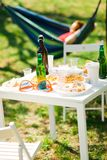 Tabelle mit Flaschen Bier und Nahrung auf Sommergartenfest stockfotografie
