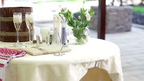 Tabelle mit Hochzeitszubehör und zwei Gläsern Champagner stock video