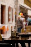 Tabelle mit Kaffeetasse und Glas Wasser im Mengenplatz Stockbilder