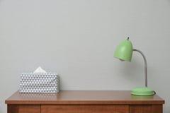Tabelle mit Lampe und Gewebe Stockfotografie