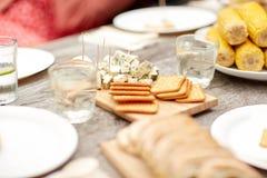 Tabelle mit Lebensmittel für Abendessen am Sommergartenfest Lizenzfreie Stockfotografie