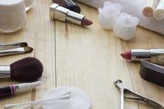 Tabelle mit Make-up, Bürsten, Lippenstift und Creme Stockbilder