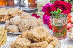 Tabelle mit marokkanischen Plätzchen und Tee Stockbilder