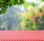 Tabelle mit roten Tischdecken- und Unschärfebäumen mit bokeh Hintergrund Stockfotos