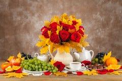 Tabelle mit Tassen Tee, Schokoladen und Rosen eines Blumenstraußes Stockfotografie