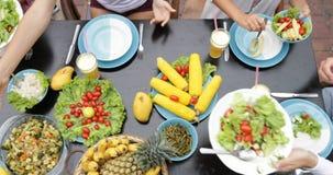 Tabelle mit Tellern tropische Frucht-und Salat-der Spitzenwinkelsicht-Leute-Gruppe, die zusammen gesundes vegetarisches Lebensmit stock video footage