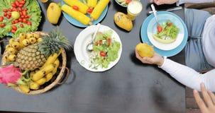 Tabelle mit Tellern tropische Frucht-und Salat-der Spitzenwinkelsicht-Leute-Gruppe, die zusammen gesundes vegetarisches Lebensmit stock footage
