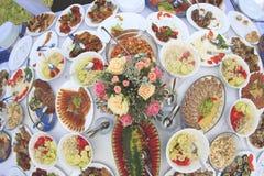 Tabelle mit zu vielem Lebensmittel und Blume in der Mitte Lizenzfreies Stockfoto