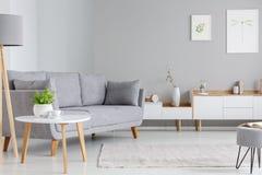 Tabelle nahe bei grauem Sofa im scandi Wohnzimmerinnenraum mit Beitrag lizenzfreie stockfotos