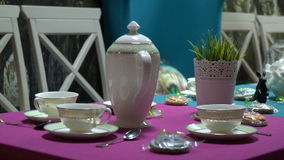 Tabelle nel corridoio di banchetto con l'insieme di tè, i biscotti e la caramella gommosa e molle nel vaso video d archivio