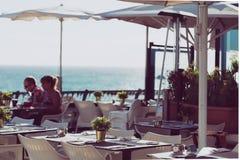 Tabelle in ristorante sulla costa di mare con le coppie che mangiano cena al fondo defocused fotografie stock libere da diritti