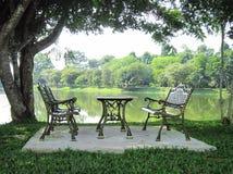 Tabelle, Stuhl und Teich im Park Stockbilder
